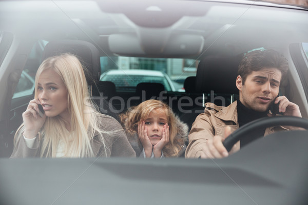 Stock photo: Sad little girl sitting in car while her parents talking