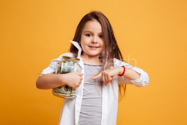 Cheerful little girl child pointing to jar with money. Stock photo © deandrobot