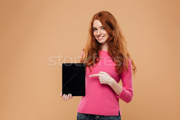 Portrait of a smiling young redhead girl pointing finger Stock photo © deandrobot