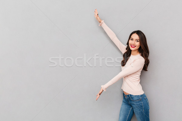 Image of pretty woman in casual showing something big with hands Stock photo © deandrobot
