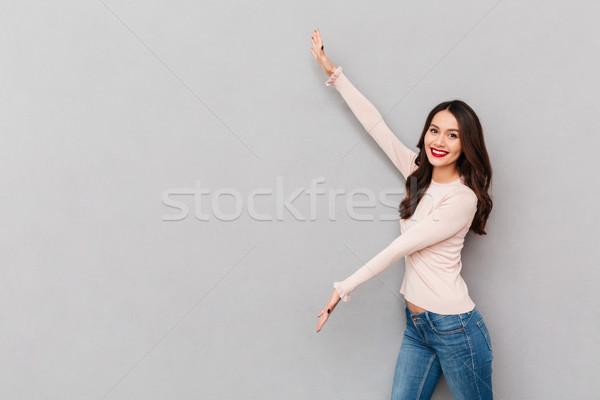 Afbeelding mooie vrouw toevallig tonen iets groot Stockfoto © deandrobot