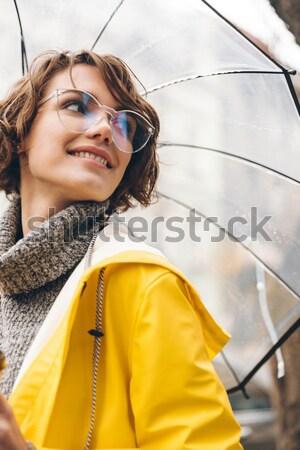 Csinos fiatal nő esőkabát kép sétál kint Stock fotó © deandrobot