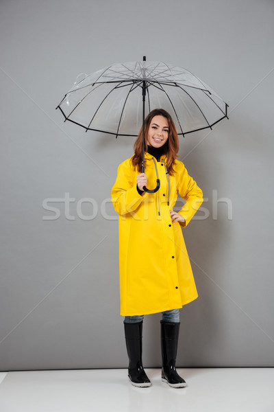 Full length portrait of a cheery girl dressed in raincoat Stock photo © deandrobot