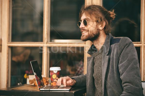 Portré mosolyog szakállas férfi fülhallgató ül Stock fotó © deandrobot