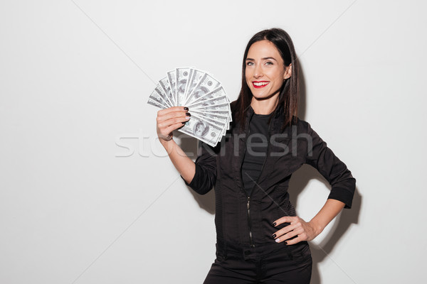 Happy woman with red lips holding money. Stock photo © deandrobot
