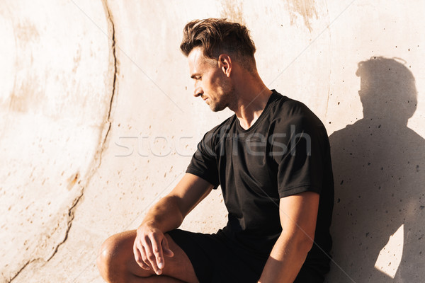 Portrait of a fit sportsman leaning on a wall Stock photo © deandrobot