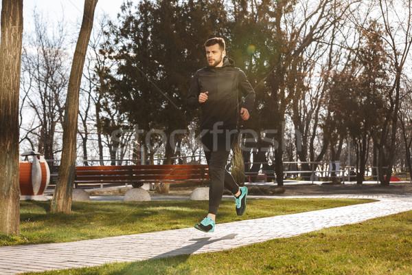 Portrait of serious young sportsman in earphones Stock photo © deandrobot