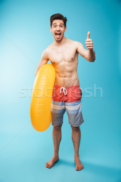 Full length portrait of an excited young shirtless man Stock photo © deandrobot