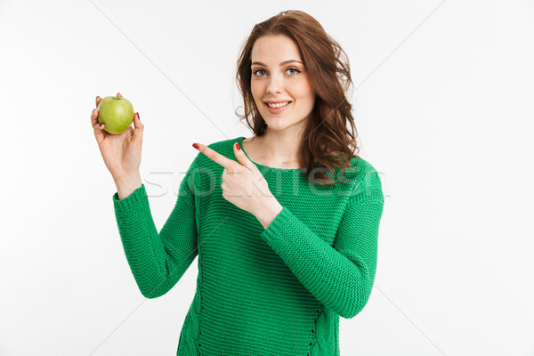 Portrait of a smiling young woman pointing finger at apple Stock photo © deandrobot