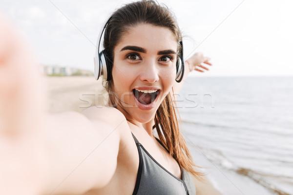 Izgatott fiatal sportoló fejhallgató elvesz kezek Stock fotó © deandrobot