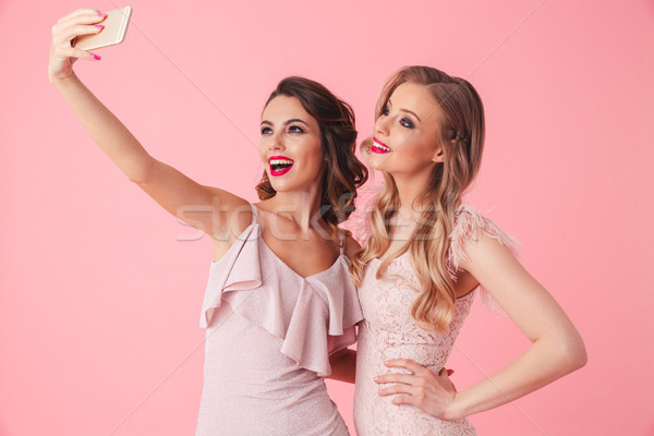 Two elegant women in dresses posing together and making selfie Stock photo © deandrobot