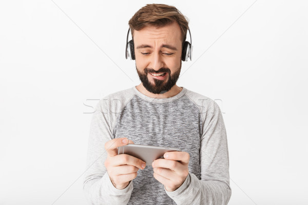 Nervioso excitado joven jugar juegos teléfono móvil Foto stock © deandrobot