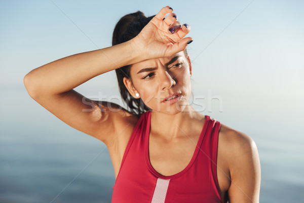 Tired sports woman relax after training and looking away Stock photo © deandrobot