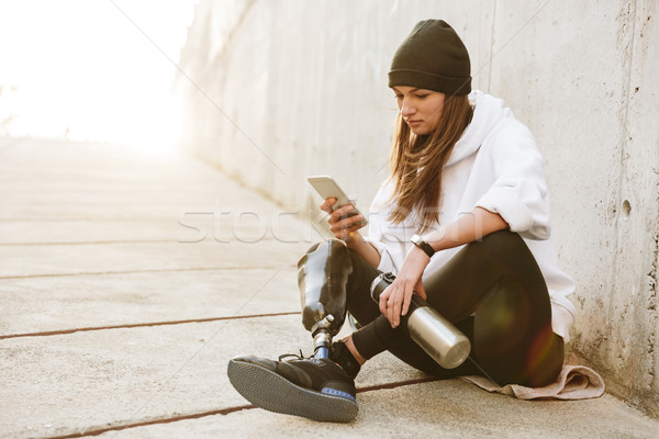 Photo of pretty young handicapped woman in streetwear having bio Stock photo © deandrobot