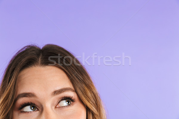 Close up half face woman looking up at copy space Stock photo © deandrobot