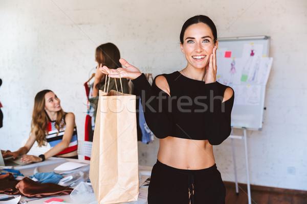 Mosolyog fiatal nő szabó mutat papírzacskó stúdió Stock fotó © deandrobot