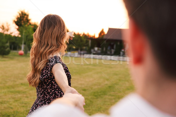 Photo from back of loving young woman holding hand of attractive Stock photo © deandrobot