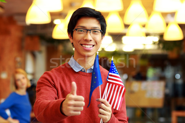 Happy asian boy in glasses holding flag of europe union with USA and showing thumb up Stock photo © deandrobot