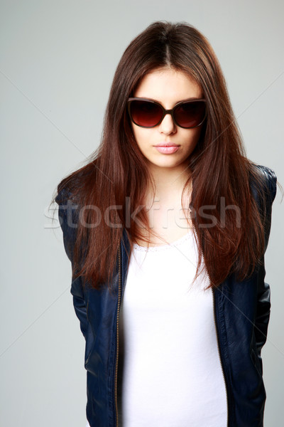 Studio shot of a young model in leather jacket and sunglasses on gray background Stock photo © deandrobot