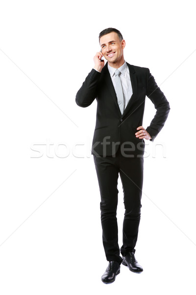 Full-length portrait of a happy businessman talking on the phone over white background Stock photo © deandrobot