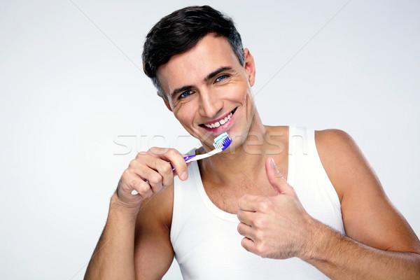 Boldog férfi fogmosás szürke orvosi háttér Stock fotó © deandrobot