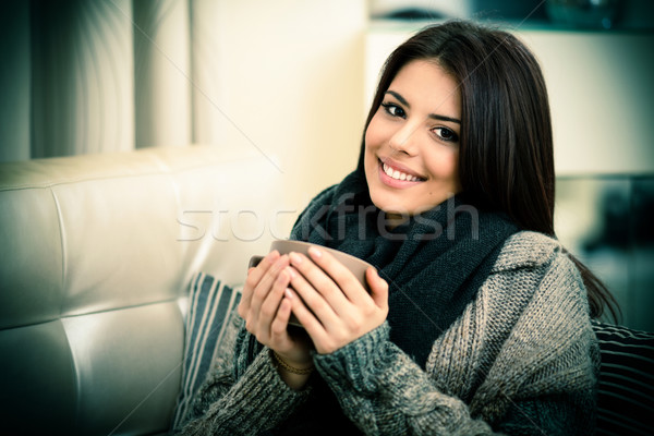 Happy young woman sitting on sofa in cozy cloths with cup of coffee Stock photo © deandrobot