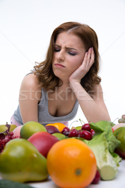 Portrait of a dissatisfied woman sitting at the table with fruits Stock photo © deandrobot
