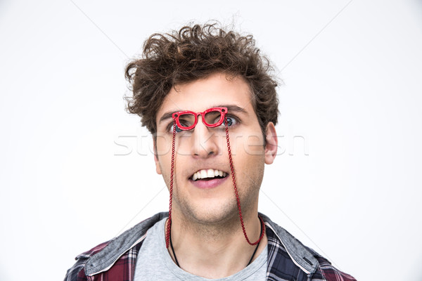 Funny man with curly hair looking through small glasses at camera Stock photo © deandrobot