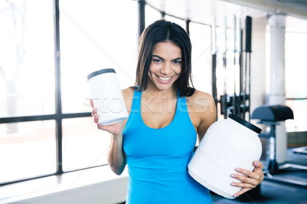 Smiling woman holding plastic container with sports nutrition Stock photo © deandrobot