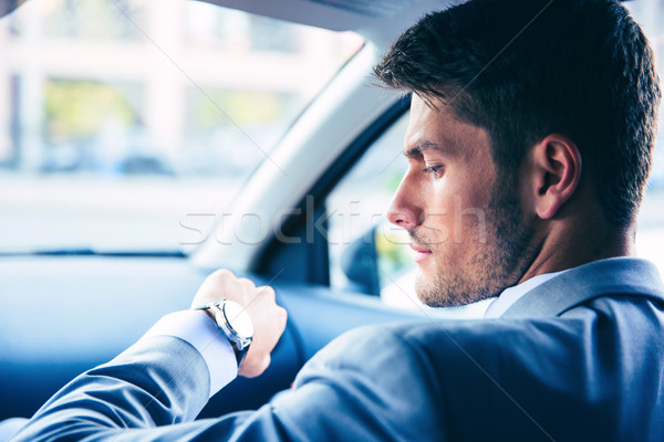 Businessman looking on wrist watch Stock photo © deandrobot