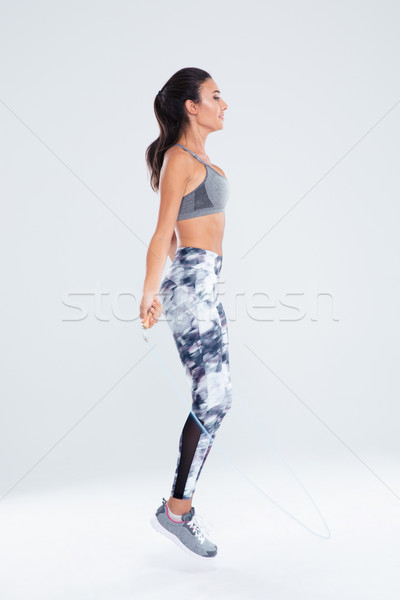 Fitness woman jumping on skipping rope Stock photo © deandrobot