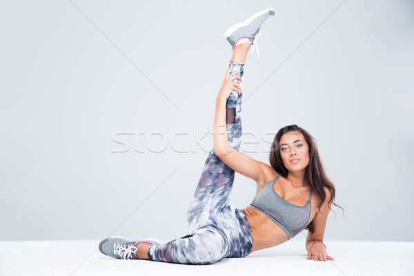 Fitness woman stretching legs on the floor Stock photo © deandrobot