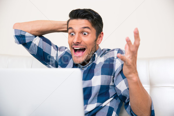 Excited man sitting on the sofa with laptop  Stock photo © deandrobot