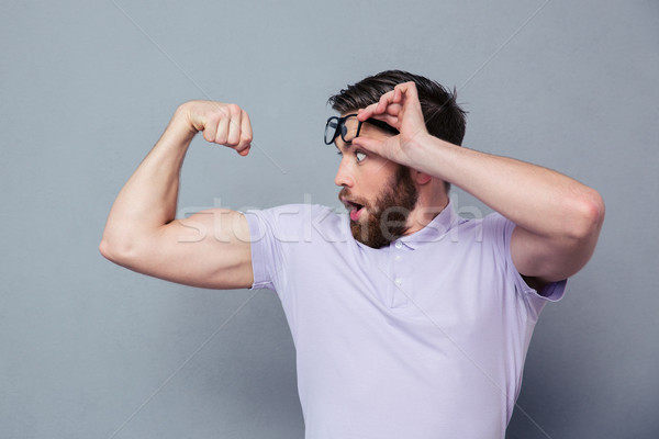 Man looking at his biceps with delight  Stock photo © deandrobot