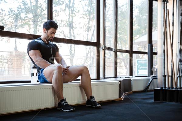 Fitness man listening to music sitting on windowcill Stock photo © deandrobot