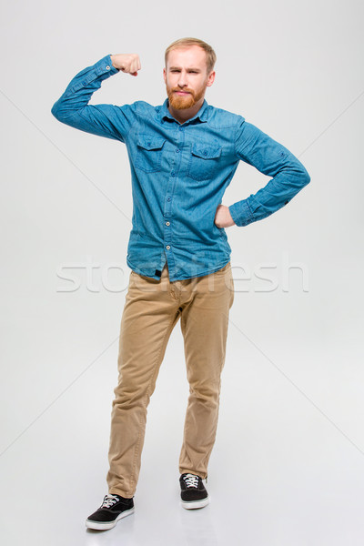 Amusing bearded man showing his muscles  Stock photo © deandrobot