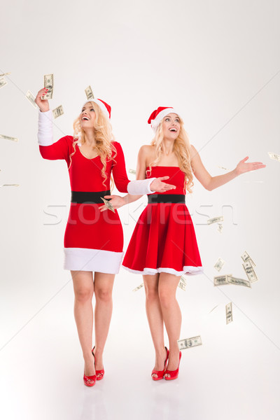 Money fallen around excited sisters twins standing and smiling  Stock photo © deandrobot