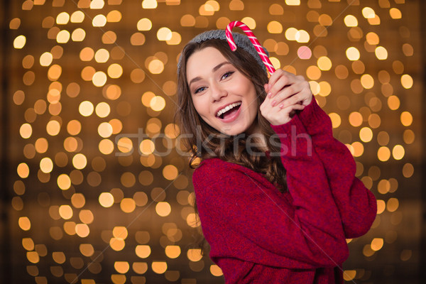 Cheerful attractive young woman holding sweet candy cane and smiling  Stock photo © deandrobot
