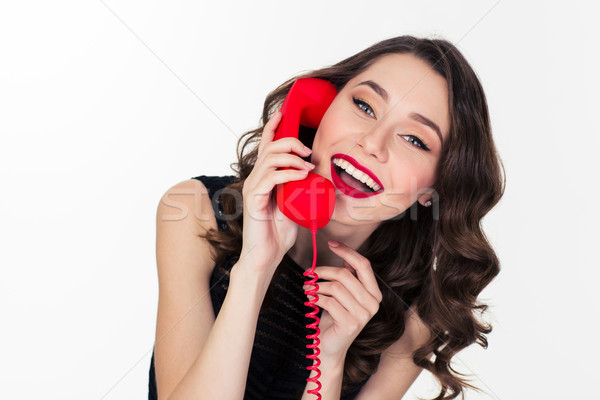 Cheerful attractive curly retro styled woman talking on red telephone  Stock photo © deandrobot