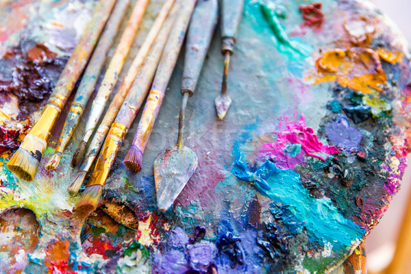 Bright mixed color paints on art palette with paintbrushes  Stock photo © deandrobot