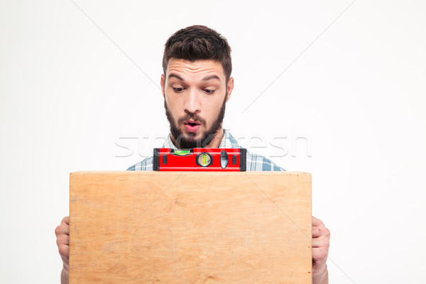 Amusing concentrated young bearded man using bubble level  Stock photo © deandrobot