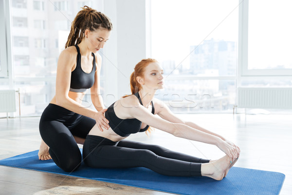 Woman sitting and stretching with her coach Stock photo © deandrobot