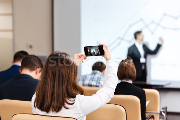 Businesswoman making video with mobile phone on business conference Stock photo © deandrobot