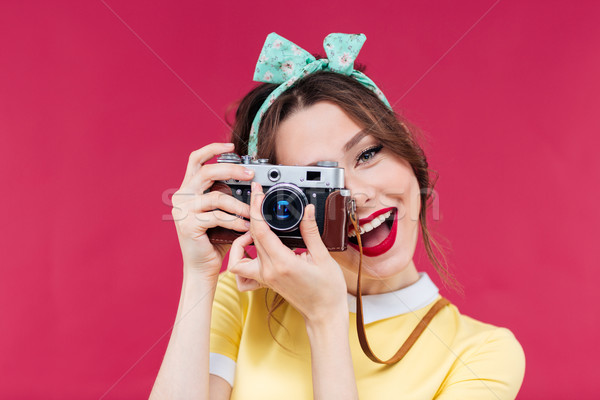 Smiling attractive young woman taking photos using old camera Stock photo © deandrobot