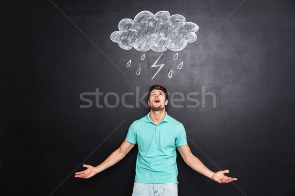 Young angry man shouting over blackboard with drawn raincloud Stock photo © deandrobot