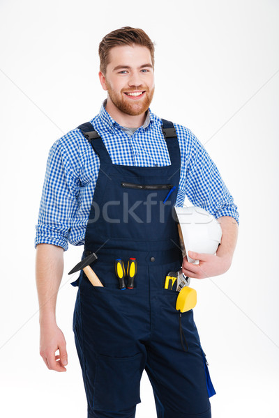 Cheerful handsome young builder in overall standing and holding helmet Stock photo © deandrobot