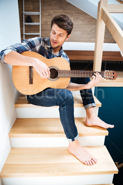 Man with guitar sitting indoors Stock photo © deandrobot