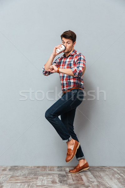 Wondered young man drinking takeaway coffee and looking at wristwatch Stock photo © deandrobot