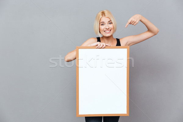 Smiling woman holding blank white board and pointing on it Stock photo © deandrobot