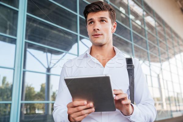 Pensieroso bello giovani imprenditore piedi tablet Foto d'archivio © deandrobot
